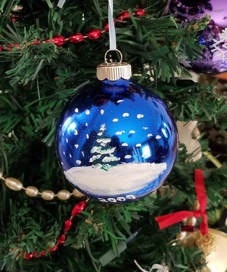 Shiny blue ornament with snowy tree scene