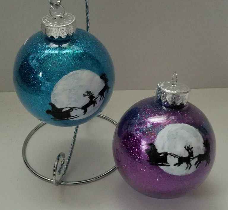 2 ornaments with hand-painted santa silhouette on moon - one purple glitter background, one blue glitter background