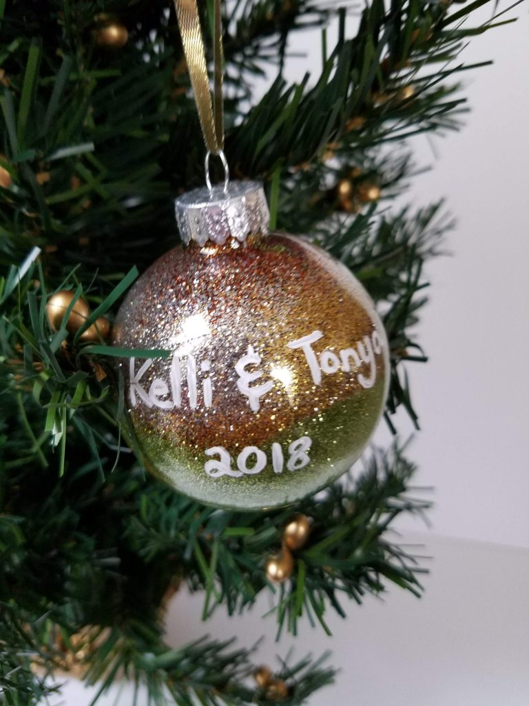 Multicolored glitter ornament - silver, orange, yellow, green. White lettering Kelli & Tonya 2018