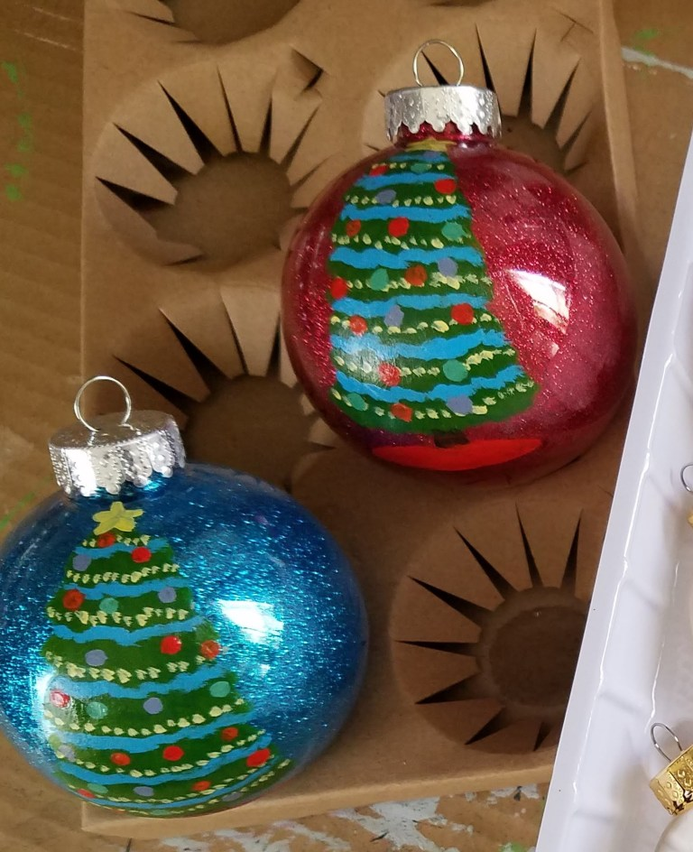 2 ornaments with handpainted christmas tree - one red glitter background, other blue glitter background