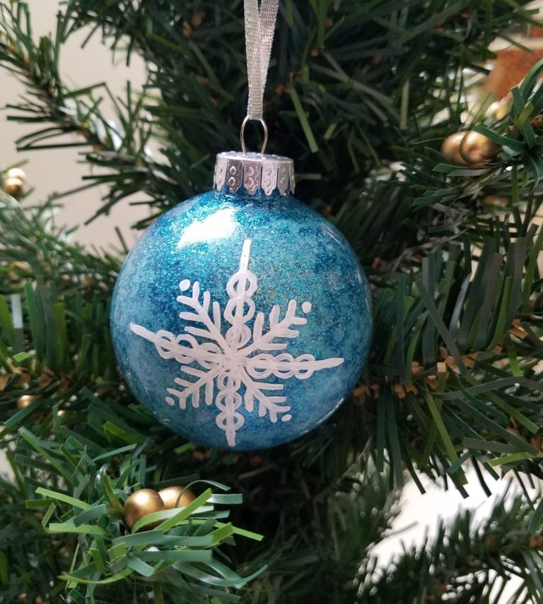 Light blue glitter ornament, white hand-painted snowflake hanging on tree