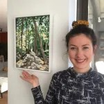 """Picture depicting Laura next to her painting """"Forest Light"""", which depicts a forest lane of beech trees in the vicinity of Bruges, Belgium"""