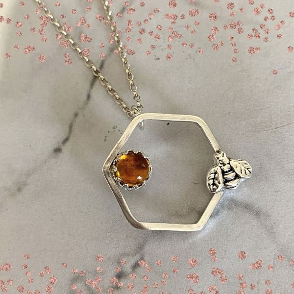 Silver pendant with bee charm and amber gemstone