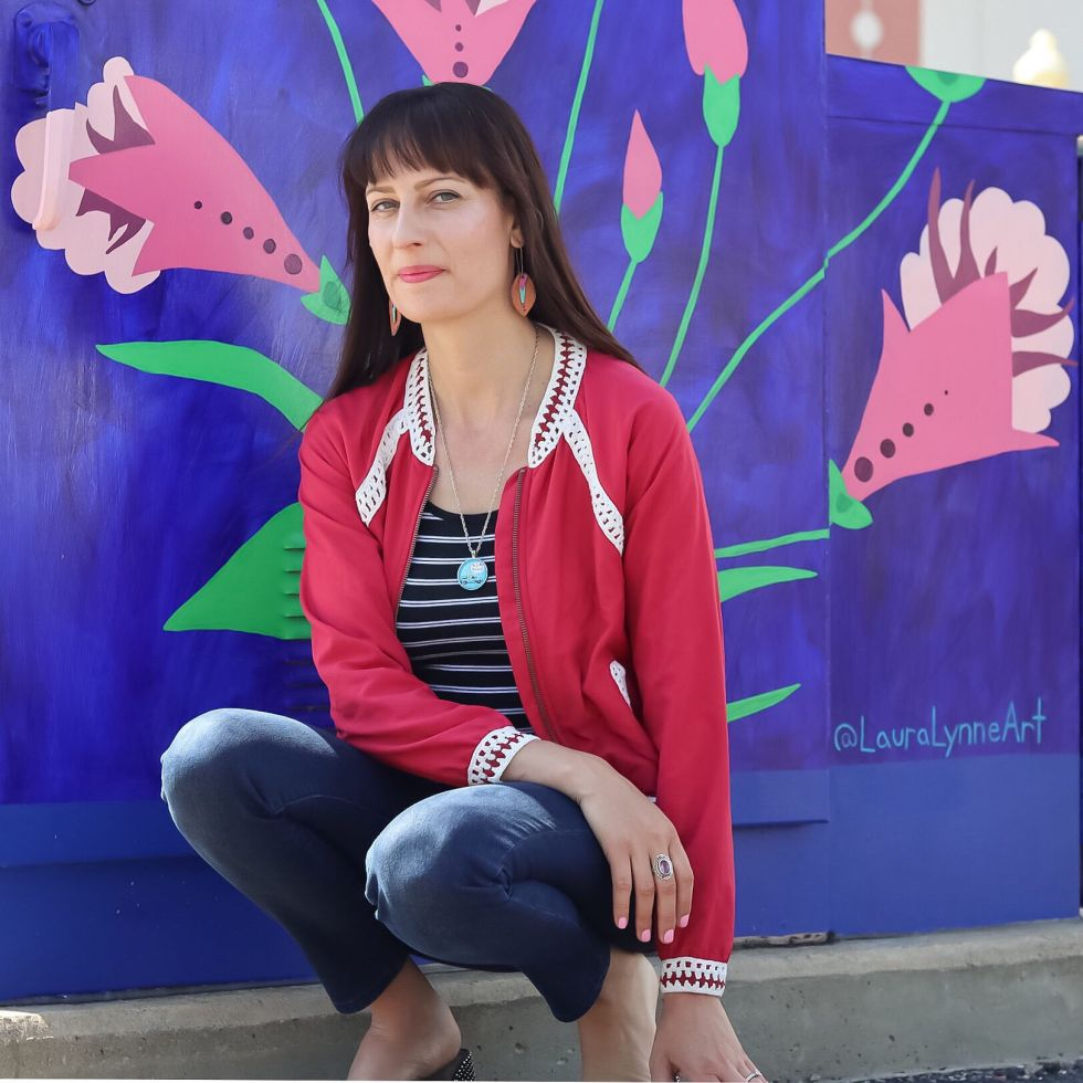 Laura Lynne artist portrait in front of bloom where you are planted mural