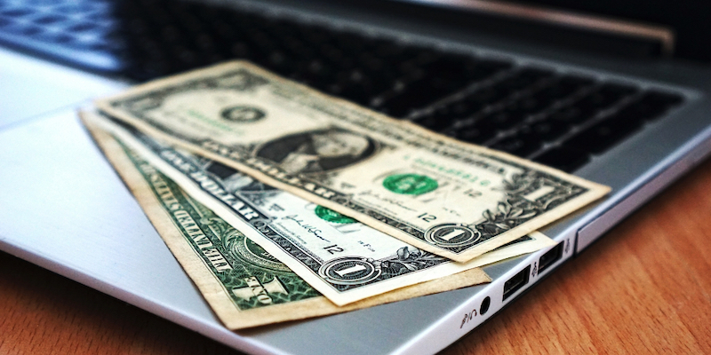 dollar bills on laptop computer