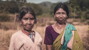 two indian women with tattooed faces standing in a field
