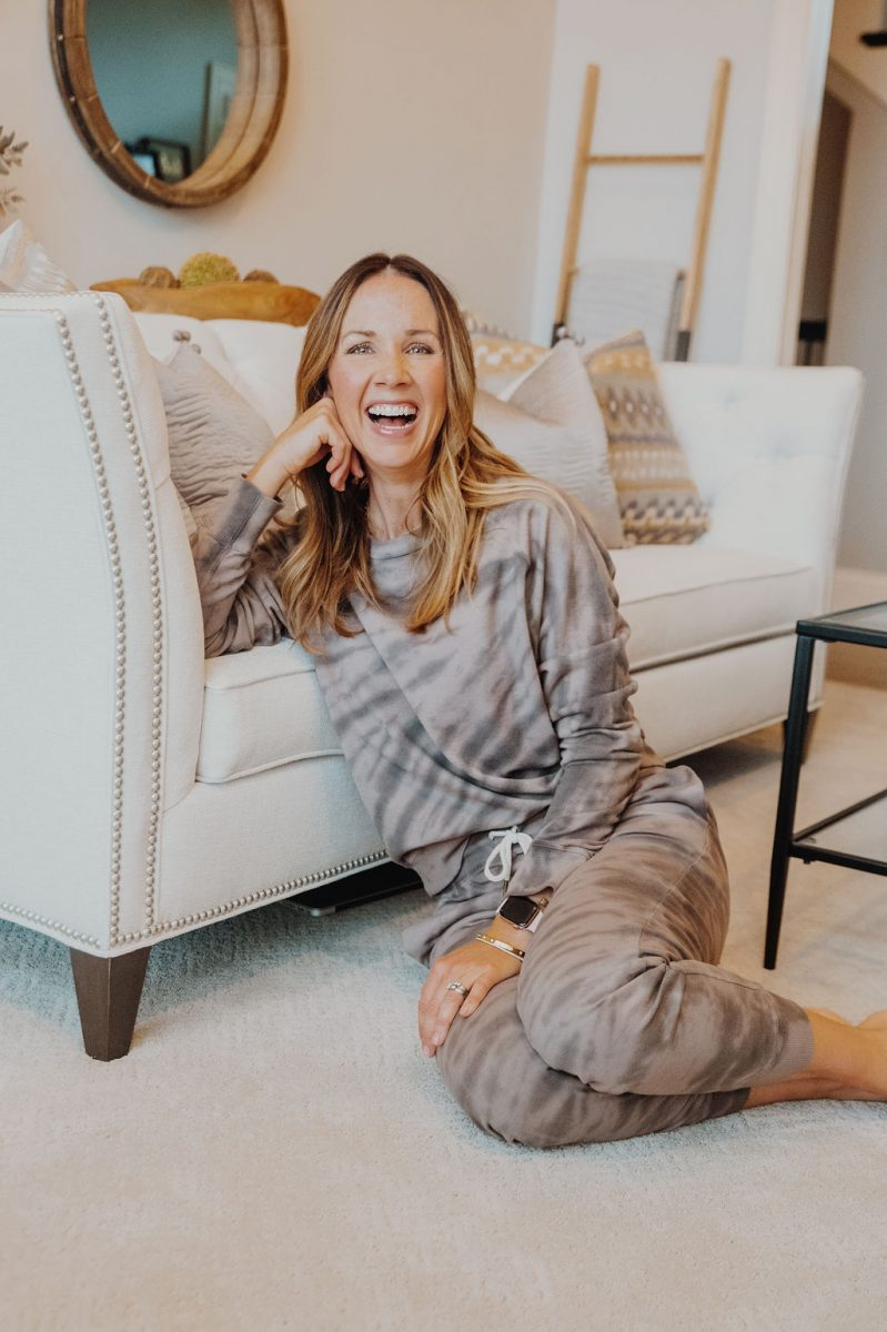 Laura in tie dye sweatsuit, leaning against cream couch, open mouth laughing