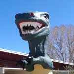 front view of very toothy ugly green concrete dinosaur