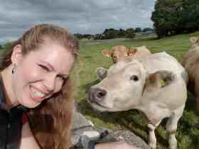 Laura seflie-ing with a curious light cow.