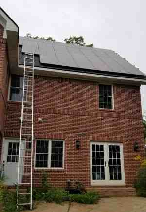 two-story brick house with ladder to roof and solar panels