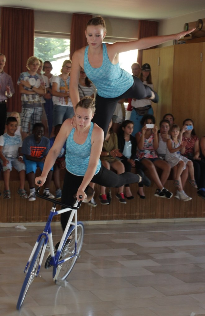 Two gymnasts riding the same bike. One standing on 1 leg with 1 arm in the air.