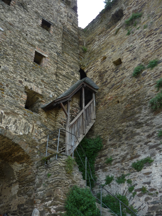 Stone castle walls with skinny steep wooden staircase (half-covered with wooden roof)