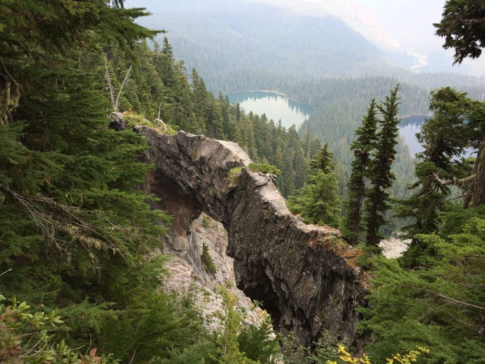 Natural bridge in the Mount Rainier National Park backcountry, with Lake James and Lake Edith in the distance.