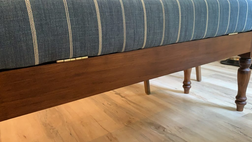 back side of hinged storage bench with blue striped upholstered cushion