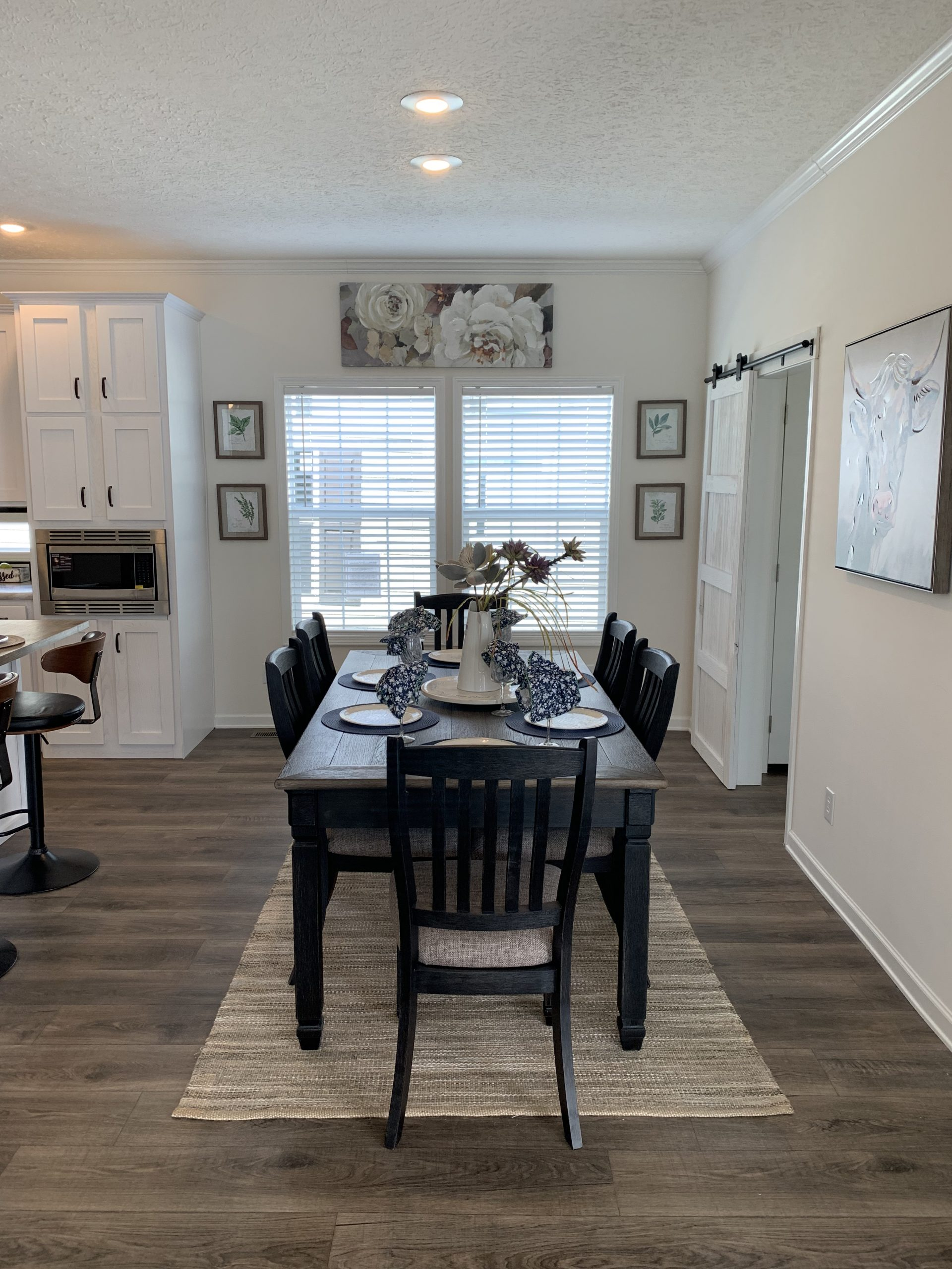 Model home kitchen with farmhouse dining table, black dining chairs, dining table tables cape, floral art hanging above windows, neutral area rug.