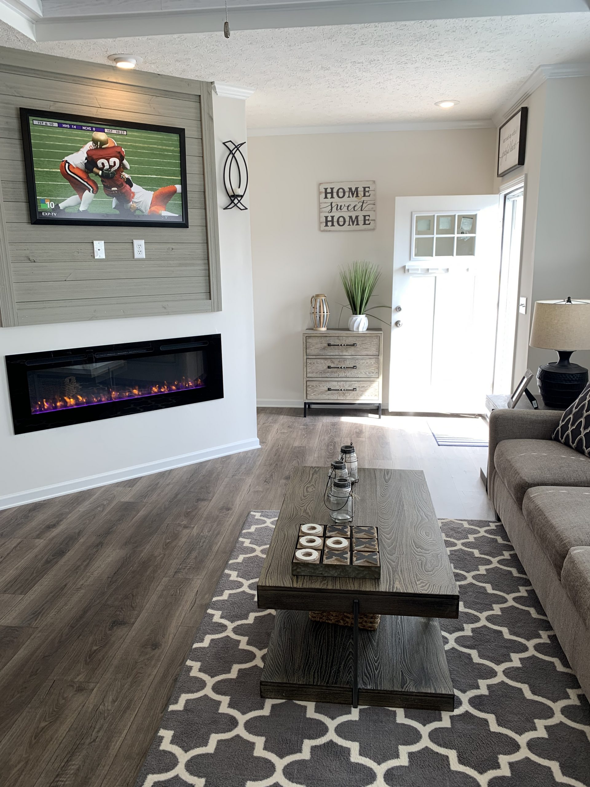 model home living room with beige sofa, farmhouse coffee table and side tables, gray and white area rug, large wall mirror, black lamps, LVP flooring.  Modern gas fireplace with wall mounted tv above.