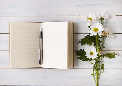 An open writers notebook with flowers on a white desktop background