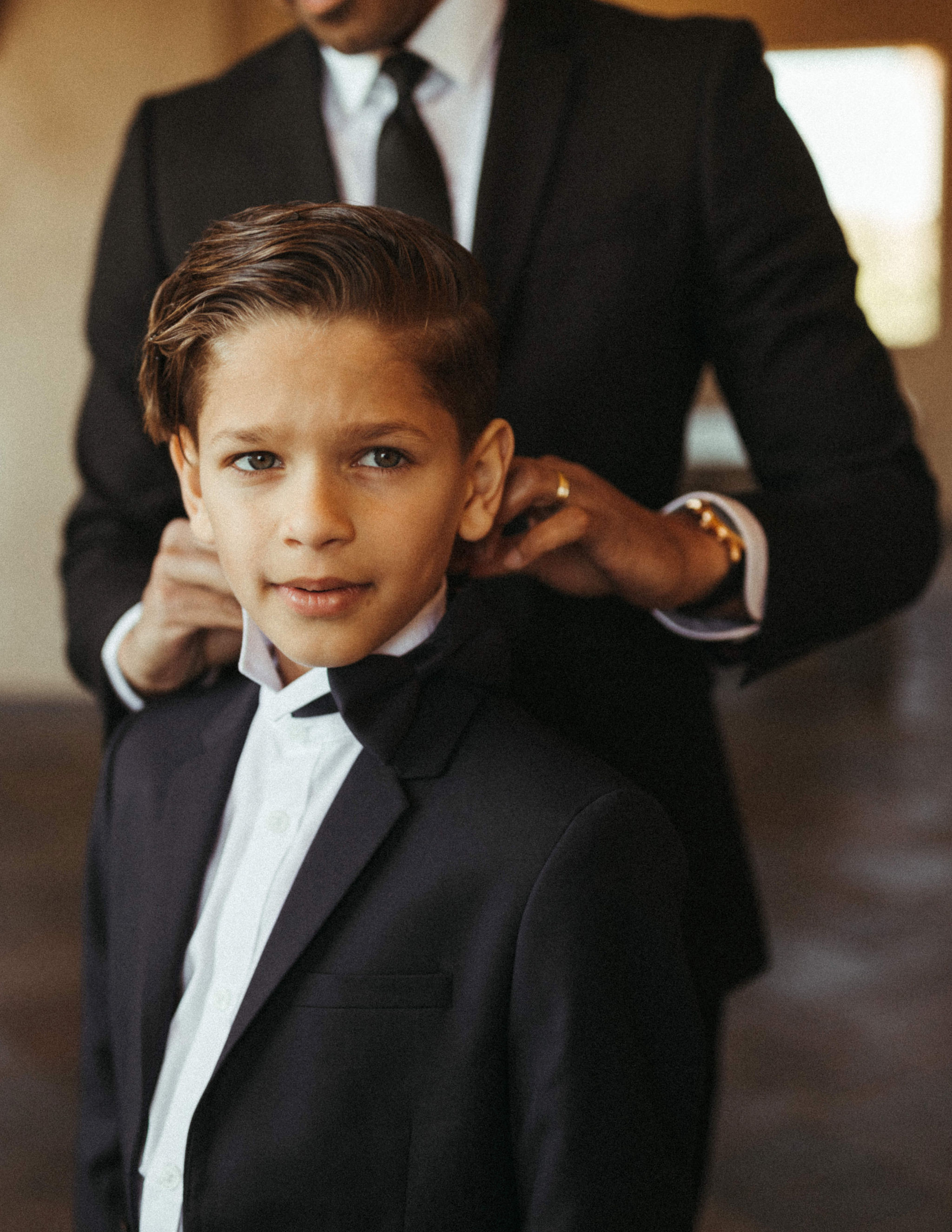 little ring bearers wearing suits and bow ties for wedding day