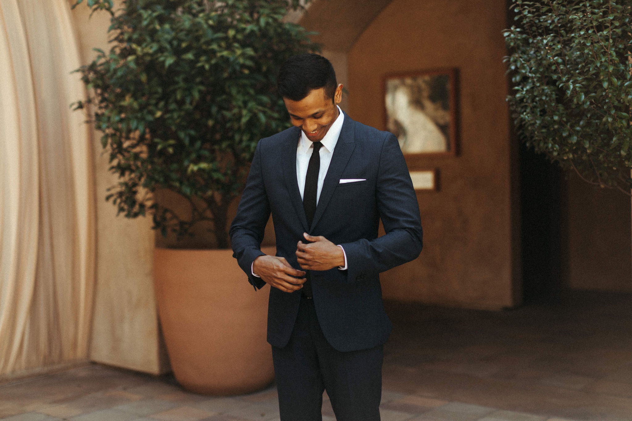 groom in navy suit and skinny black tie