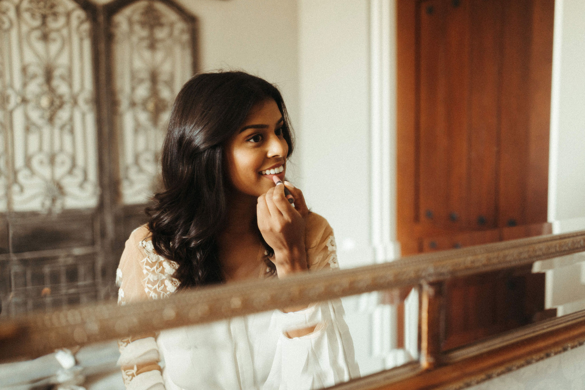 beautiful bride getting ready on her wedding day wearing lace white robe