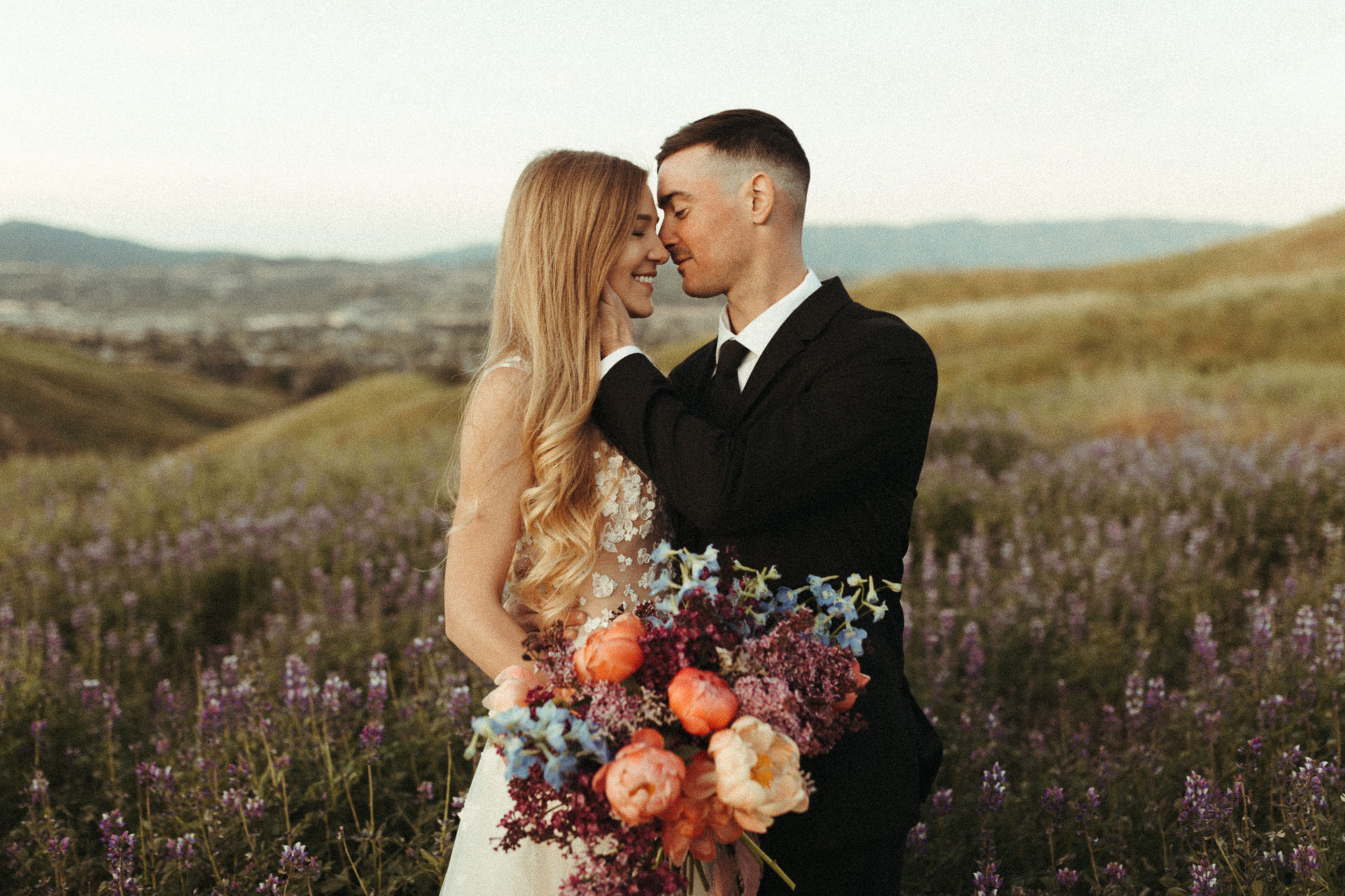 gorgeous bride and groom celebrating their wedding elopement at sunrise in some lupine fields with a beautiful romantic floral bouquet