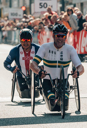 Two men in hand cycles crossing a finish line