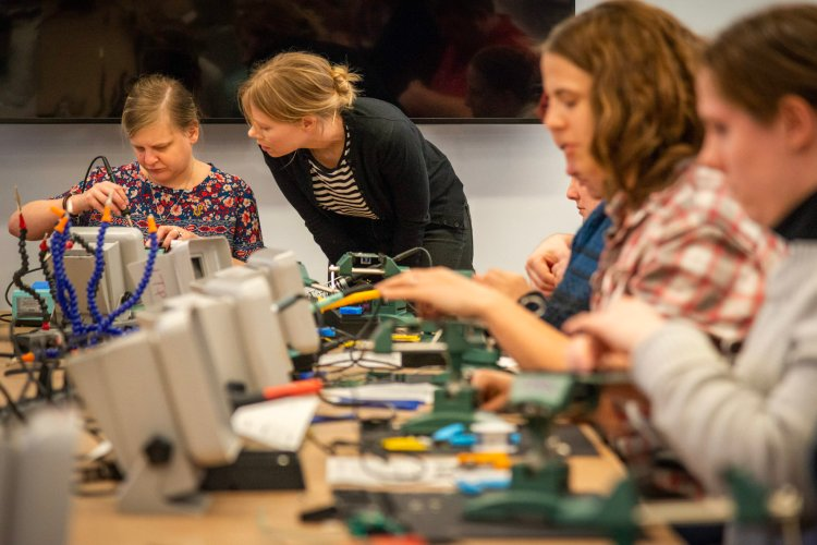 At the end of a conference table, an attendee focuses and holds their soldering iron, while a volunteer observes.