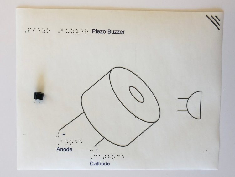 Overhead view of a tactile component diagram of a piezo. On the far left is a small, black piezo buzzer glued to the page. Next to it is an enlarged tactile graphic of a piezo with the anode and cathode labeled. On the far right is an industry symbol of a piezo: a semicircle with two parallel pins extruding from the rounded edge of the semicircle.
