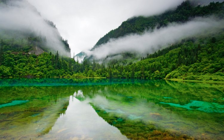 A pristine lake reflects the lush mountains that surround it.
