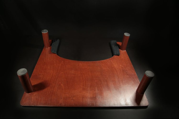 Bottom/up-side-down view of the assistive workstation, displaying the cherry wood color
