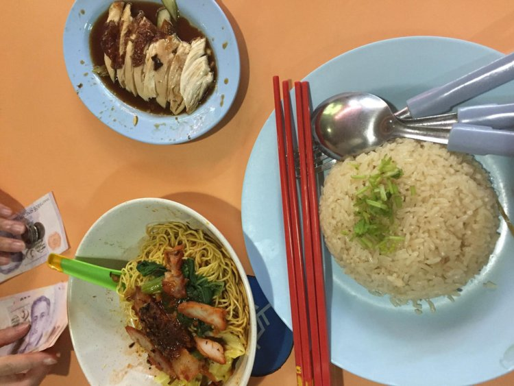 Three dishes of chicken rice at a hawker stand table