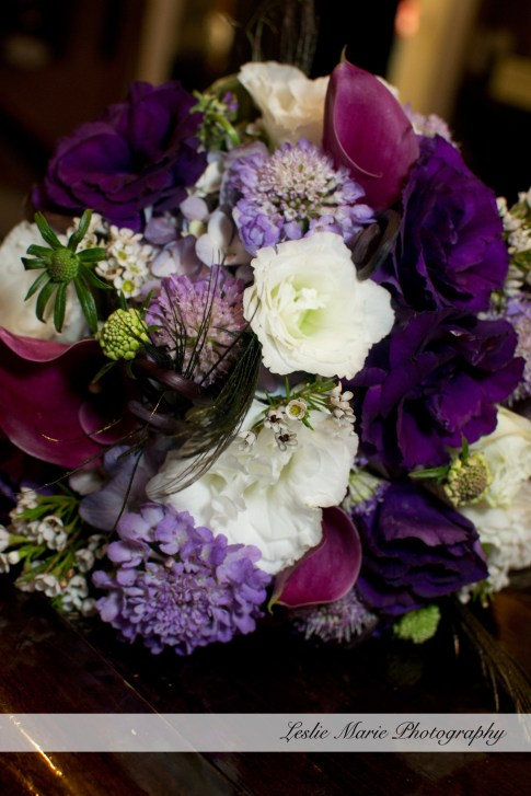purple and white bouquet with peacock feathers