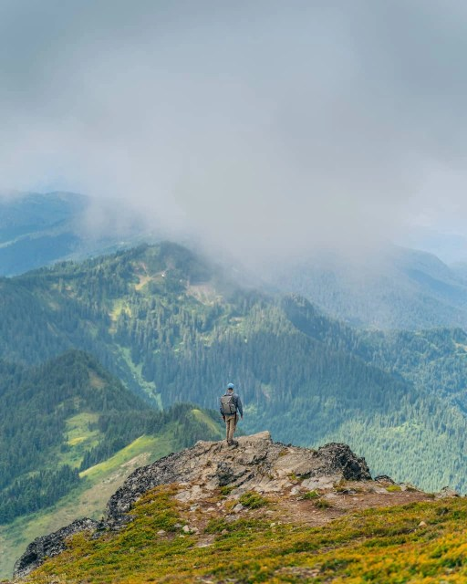 Guy at rock cliff facing Fraser Valley on Mount Cheam