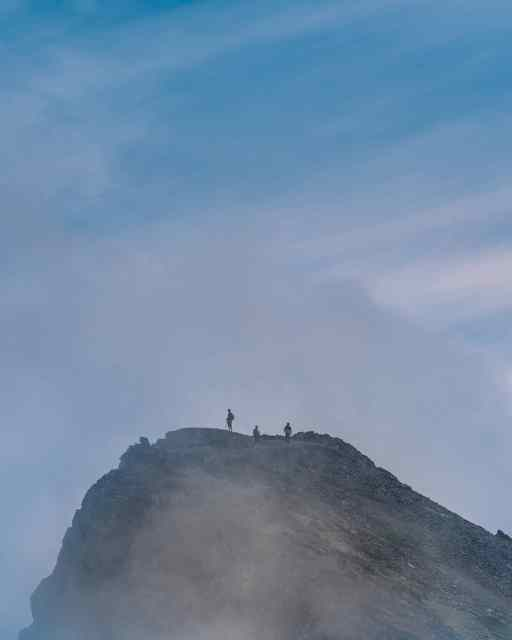 Three hikers on Cheam Peak among the clouds