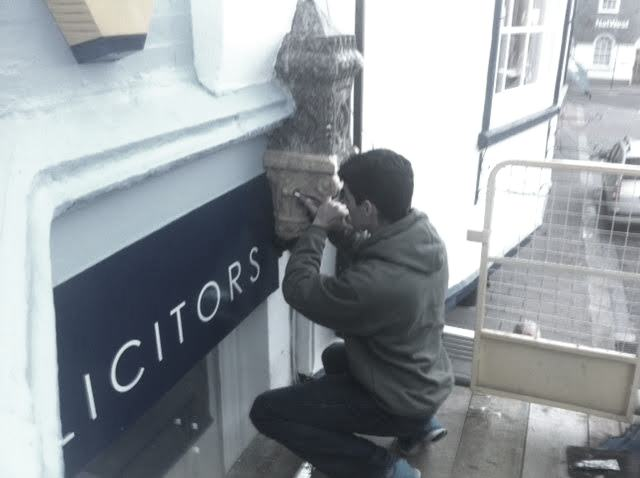 Laurent Robert woodcarver carving a capital from scaffolding, Dartmouth, Victorian shop front