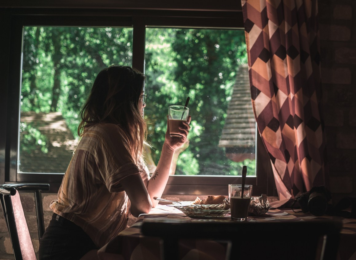 Woman sitting at a table with food in front of her looking out a window