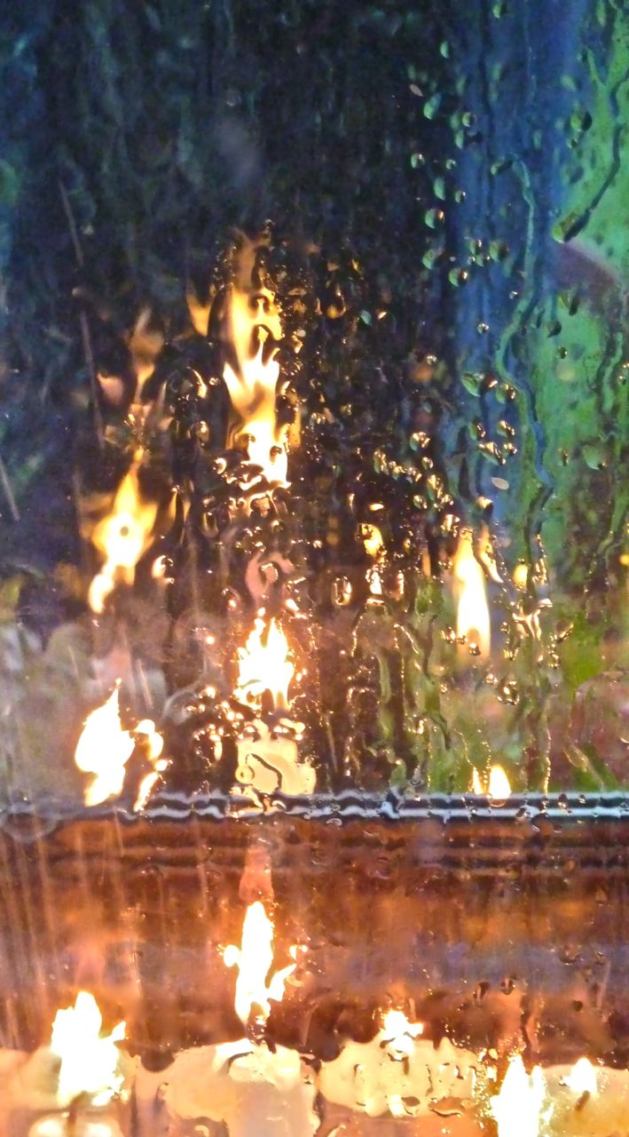 flames against a rain-streaked window