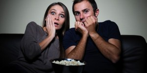 Terrified young couple watching scary movie on tv sitting in sofa