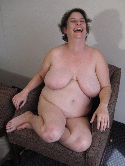 laughing nude in chair