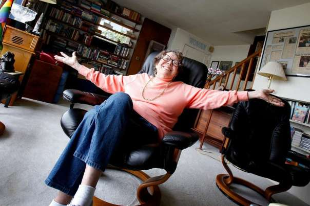Phyllis Lyon sitting back in an office chair, arms outstretched