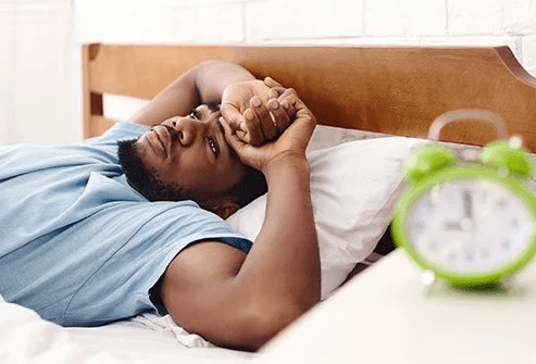 Black man in bed awake, hands clasped on forehead