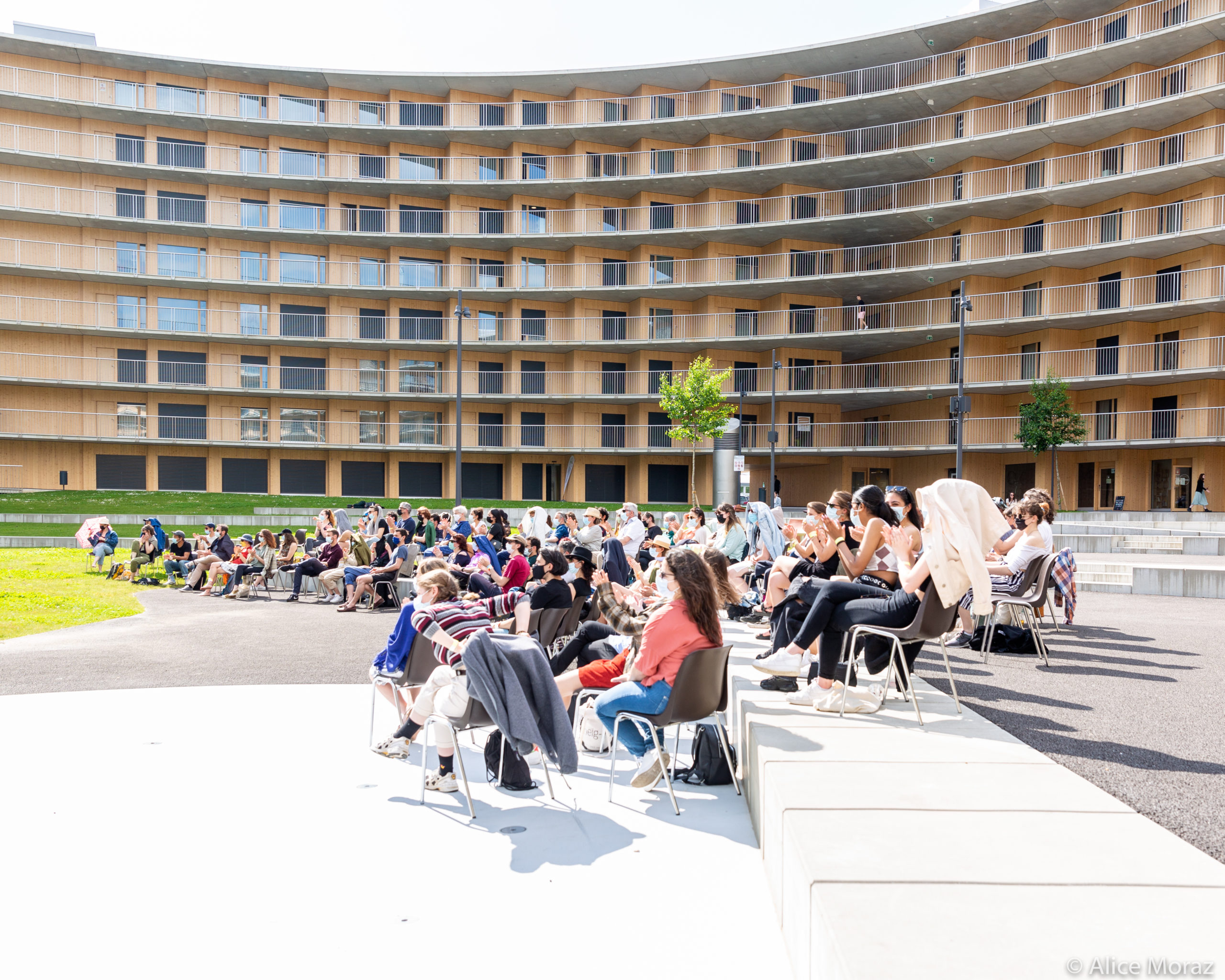 A picture of an audience sitting in the courtyard of a circular building.