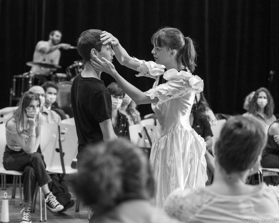 A woman in a white dress strokes the head of a man in a black t-shirt