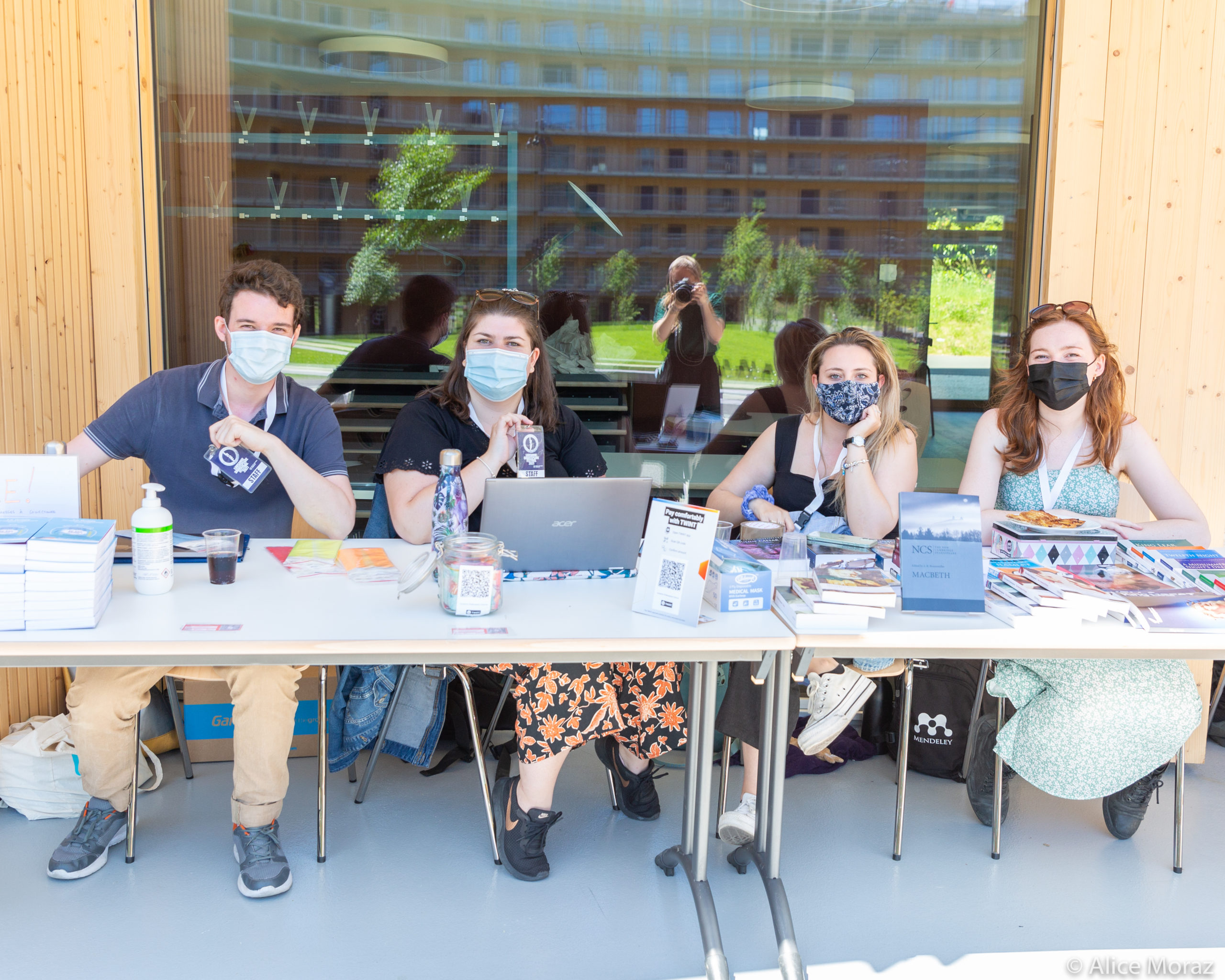 Four volunteers sit at a table. There are three women and a man. They are all wearing surgical masks.