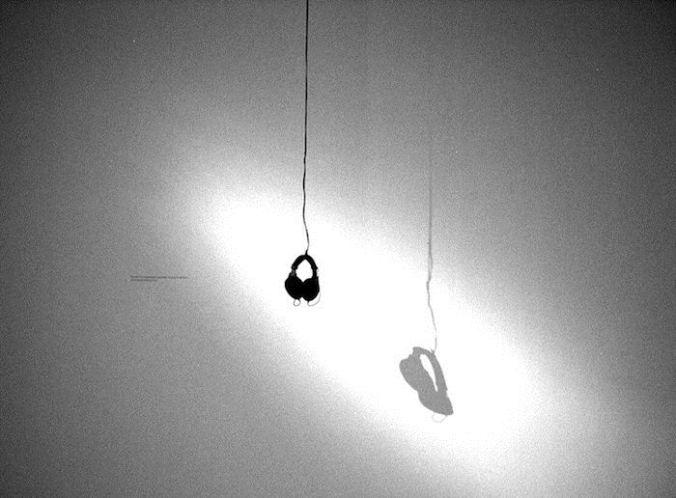 """Auriculares pendientes de un falso techo por donde se escuchaba la obra """"Trepanaciones"""", de la mexicana Teresa Margolles"""