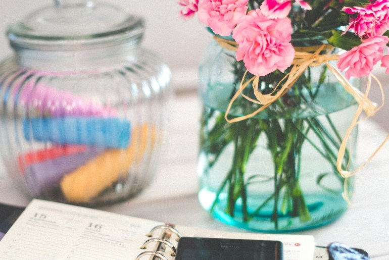 notebook and phone on desk with a vase of flowers