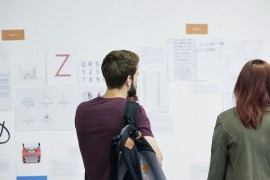 man and woman staring at work plans on the wall