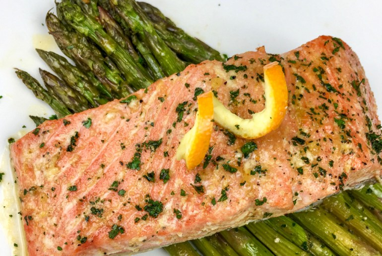 a bed of asparagus topped with Orange-Glazed Salmon