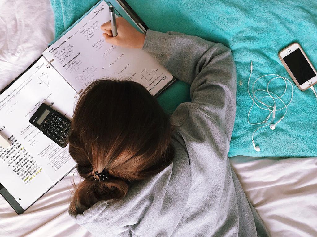 Niña haciendo deberes sobre la cama