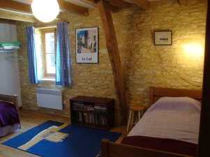 With two single beds, the third bedroom overlooks the garden, with stone walls and wooden beams.